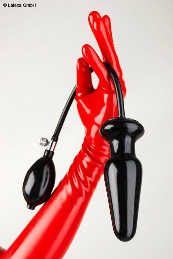 Eine Hand mit rotem Latex Handschuh hält einen aufblasbaren Analplug mit Schlauch und handpumpe
