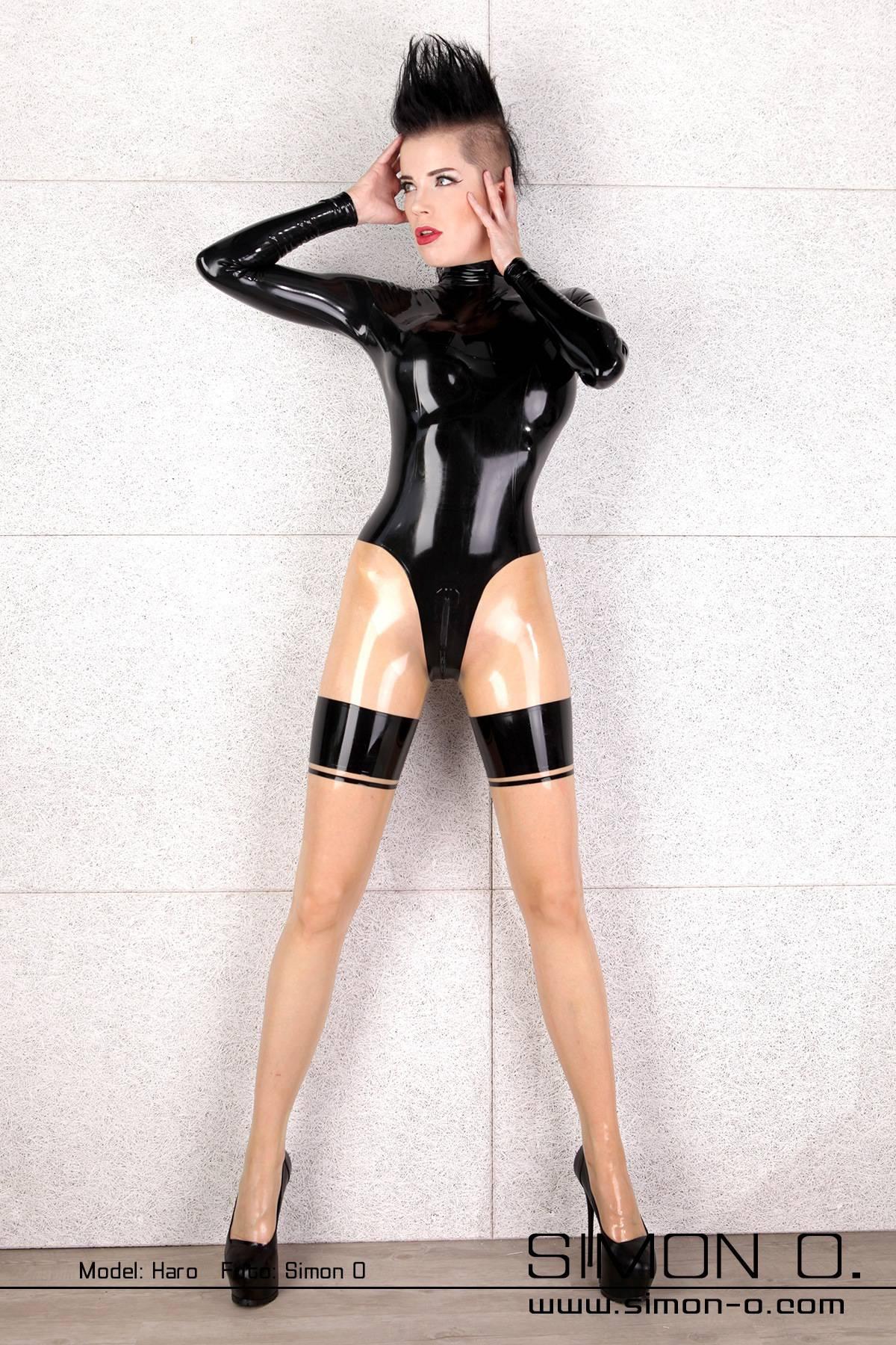 Dunkelhaarige Frau mit einem sexy glänzenden Latex Catsuit in Schwarz mit transparenten Strümpfen mit Strumpfband und Naht