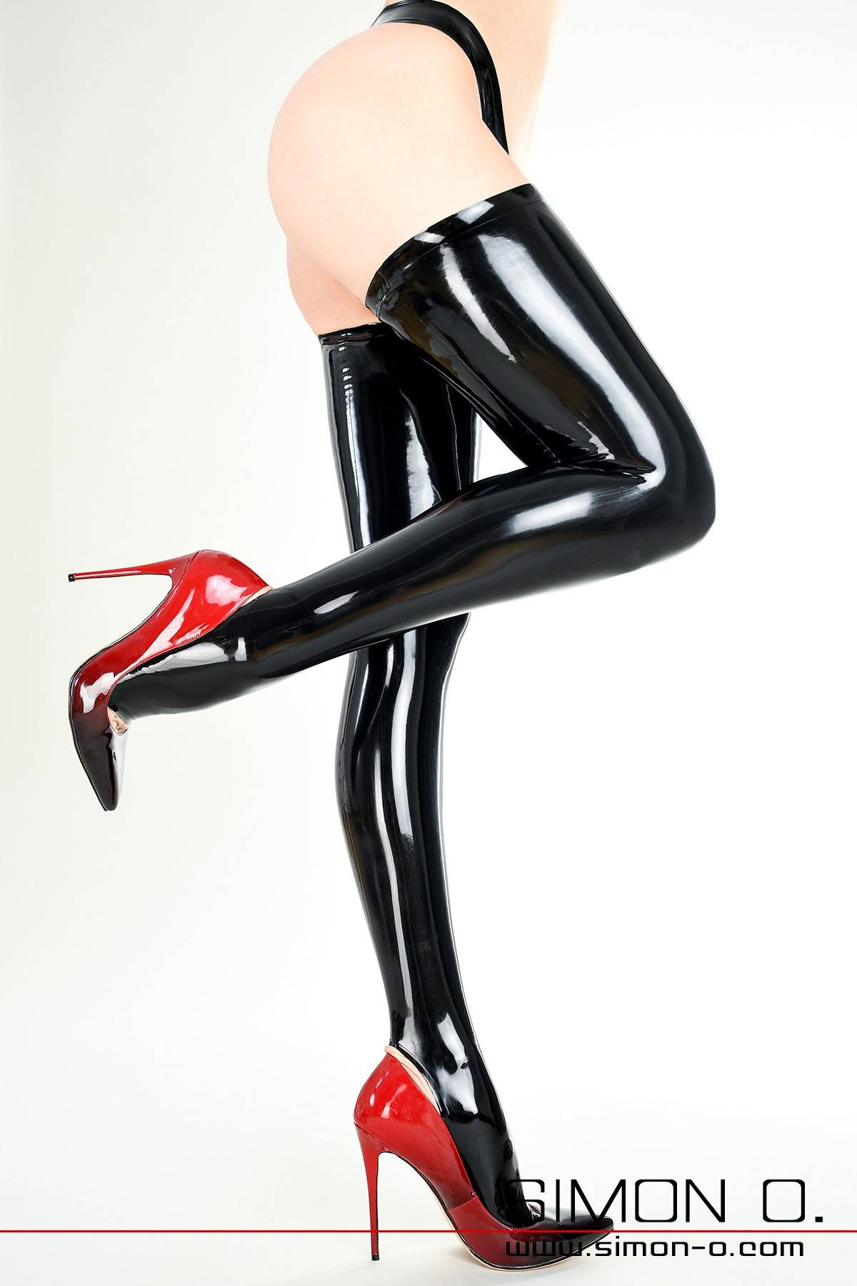 Ladies legs in shiny black stay-up latex stockings with high heels