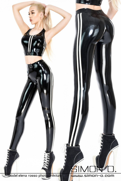 A blonde woman wears a shiny latex sports outfit. Latex leggings and top in black with white stripes