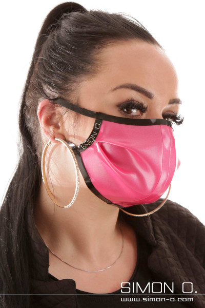 A woman is wearing a shiny latex mouth and nose guard in pink combined with black.
