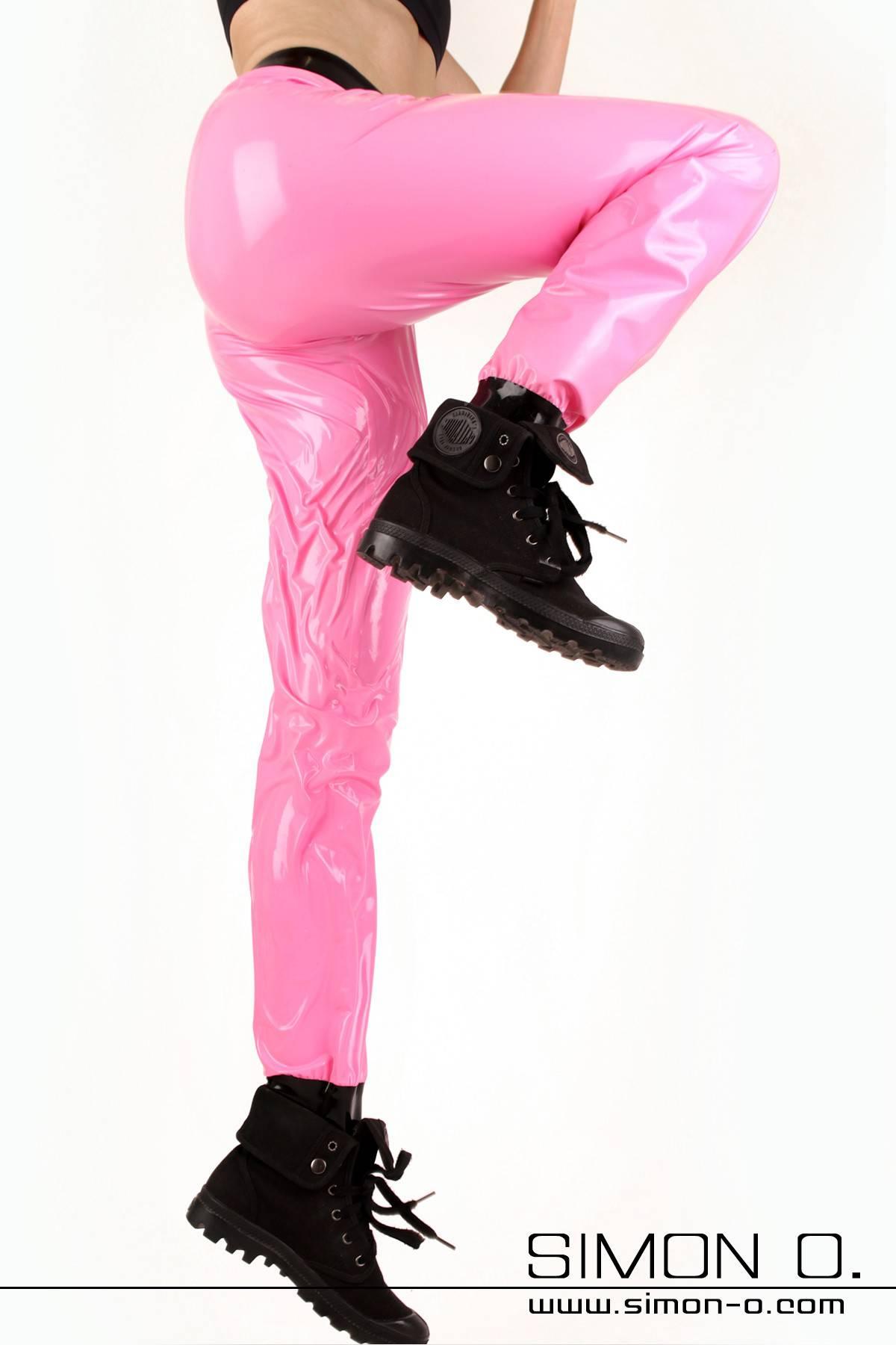 Eine Frau trägt eine lockere Glanz Trainingshose in Pink
