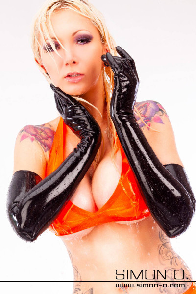 A woman wears upper arm long latex gloves in shiny black