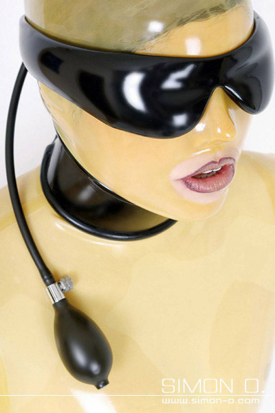 A woman wears a transparent latex mask. Over it she wears a black inflatable latex blindfold