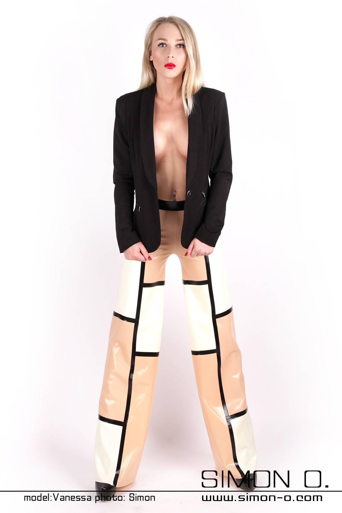 Eine Frau trägt eine Marlene Stil Latex Hose im dreifarbigen Design mit einem schwarzen Blazer kombiniert