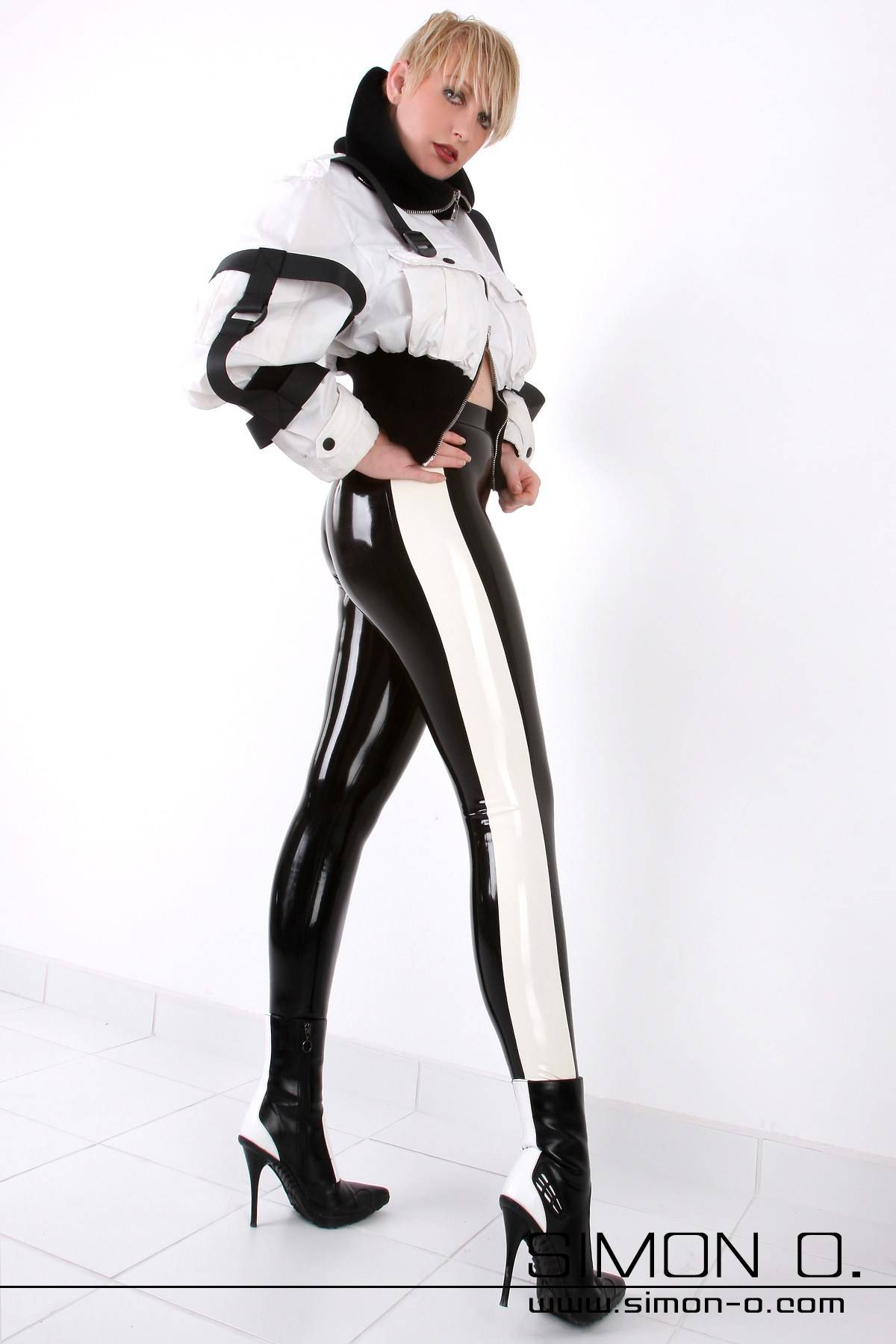 A woman in a black skintight shiny latex leggings with white stripes at the sides
