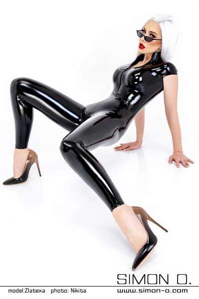 A woman wears a skintight latex catsuit in black with short sleeves