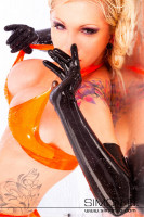 Preview: A woman wears long latex gloves seamlessly dipped in black