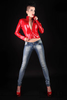 Preview: A woman wears a red rubber jacket with zipper in combination with jeans and high heels.