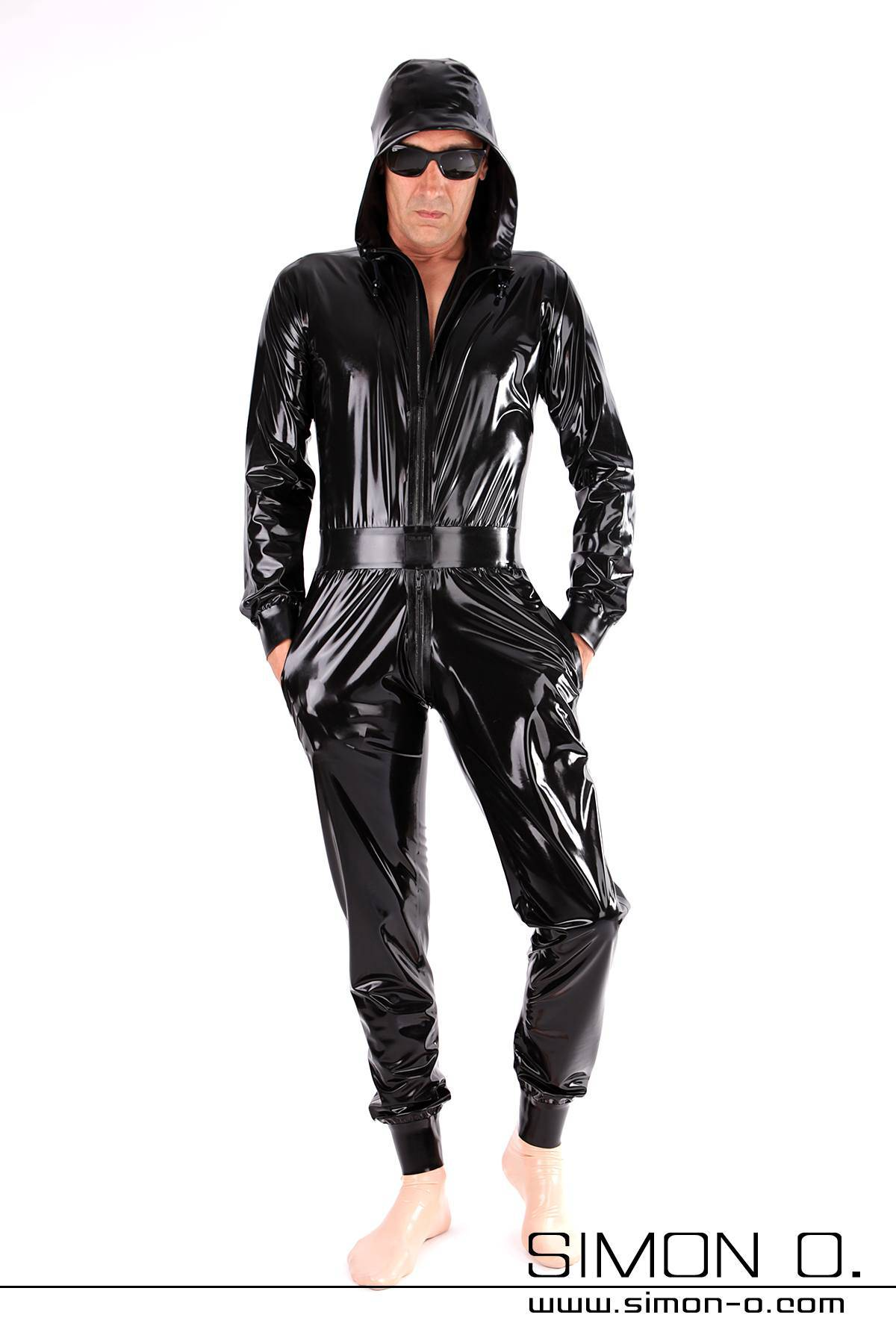 Latex overall with hood and pockets in black loosely cut but waisted with cuffs at arms and legs
