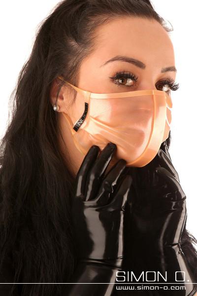 Eine Frau trägt einen nude transparenten glänzenden Latex Mund und Nasenschutz aus Latex