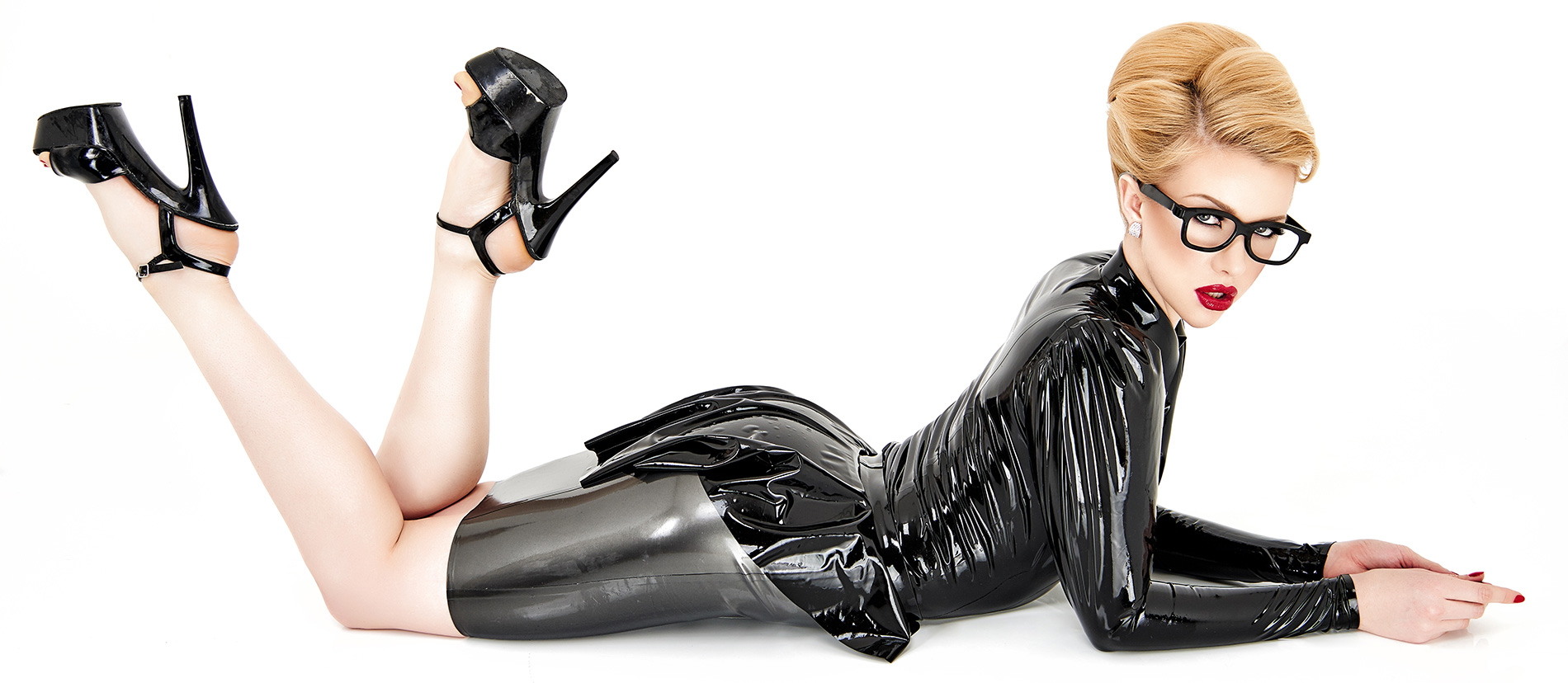 women lying on the floor with a shiny knee lenght latex skirt and High heels