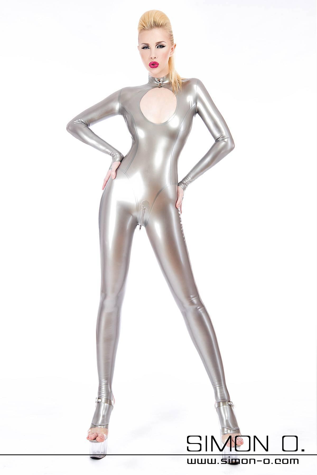 Eine blonde stehende Frau in einem glänzenden silbernen Latex Catsuit mit sexy Auschnitt
