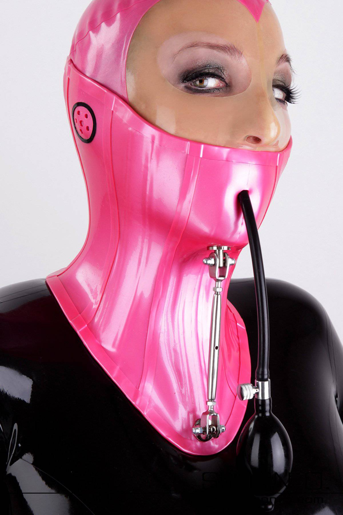 A woman with latex hood wears a high latex neck corset with adjusting screw