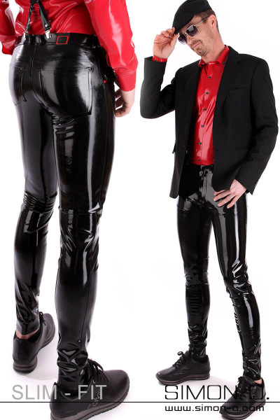 A gentleman wears a black shiny latex jean with suspenders and a red latex shirt.