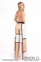 Vorschau: Eine Frau trägt eine weite Marlene Stil Latex Hose mit 3 farbigen Design von hinten gesehen