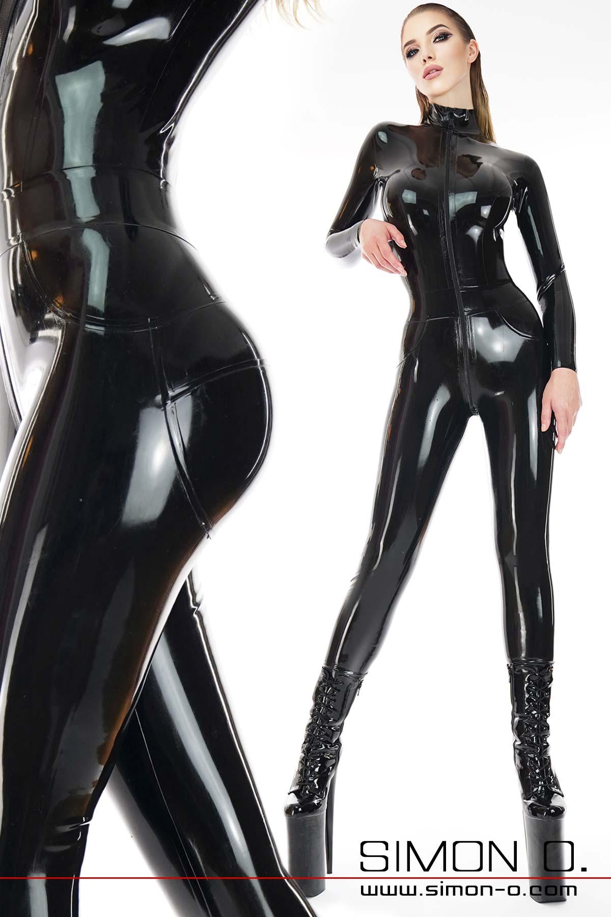 Ein Model trägt einen hautengen Latex Overall in Schwarz. Der Overall hat vorne durch den Schritt eine Zipp.
