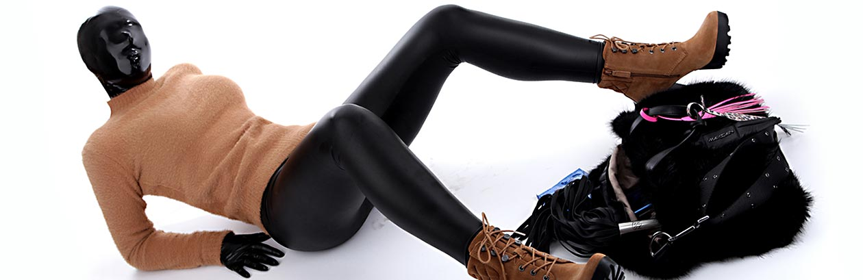 A woman with a latex hood, sweater and leggings lies on the ground with her legs spread.