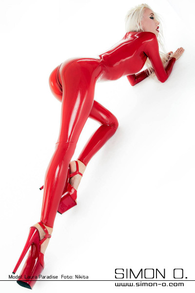 Blonde slim woman kneels in a skintight red latex catsuit with wet shiny surface