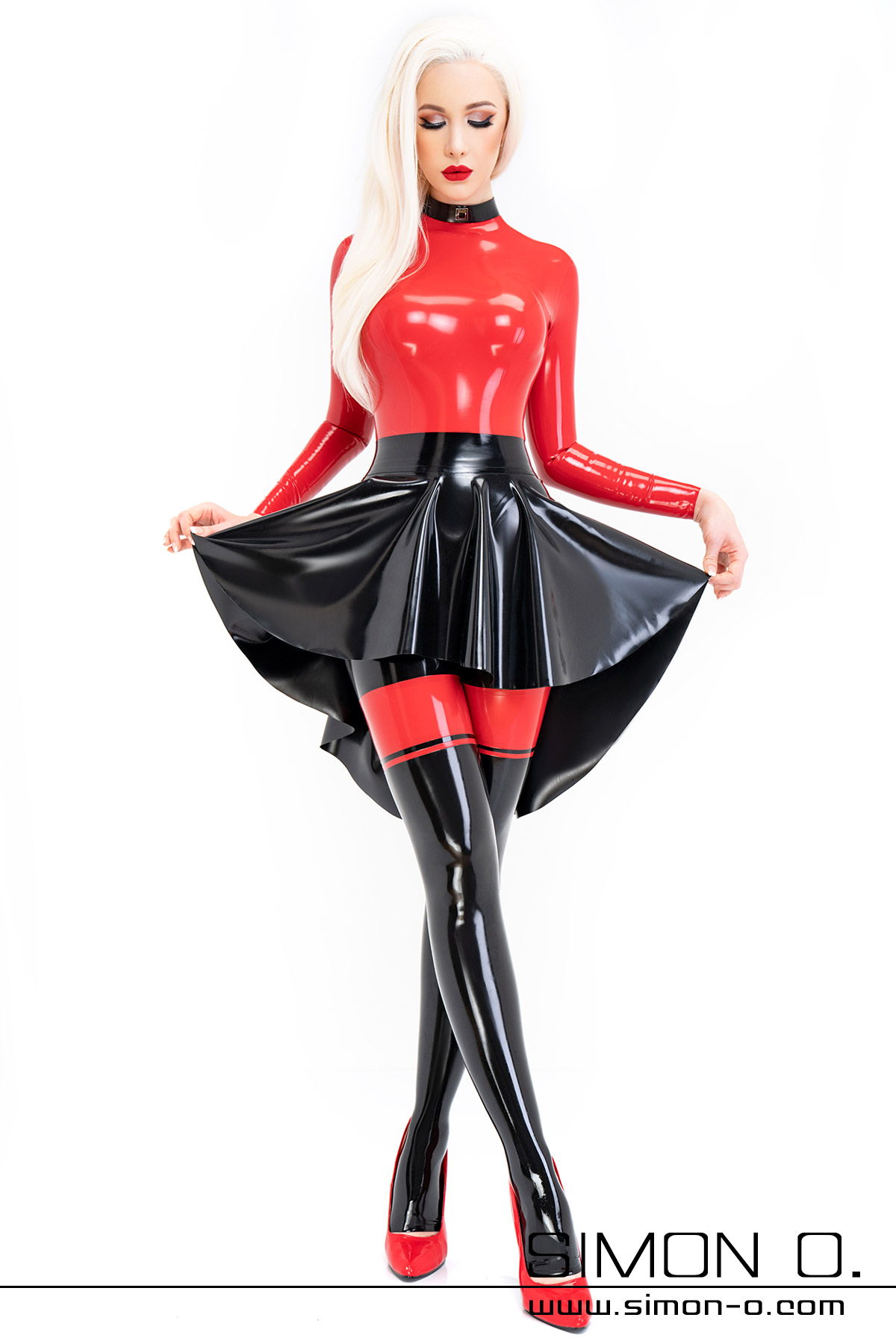 A blonde woman wears a latex plate skirt in black over a black red skintight latex catsuit