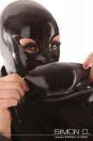 Vorschau: Eine Frau mit Latex Maske hält einen Mundschutz in Schwarz in den Händen.