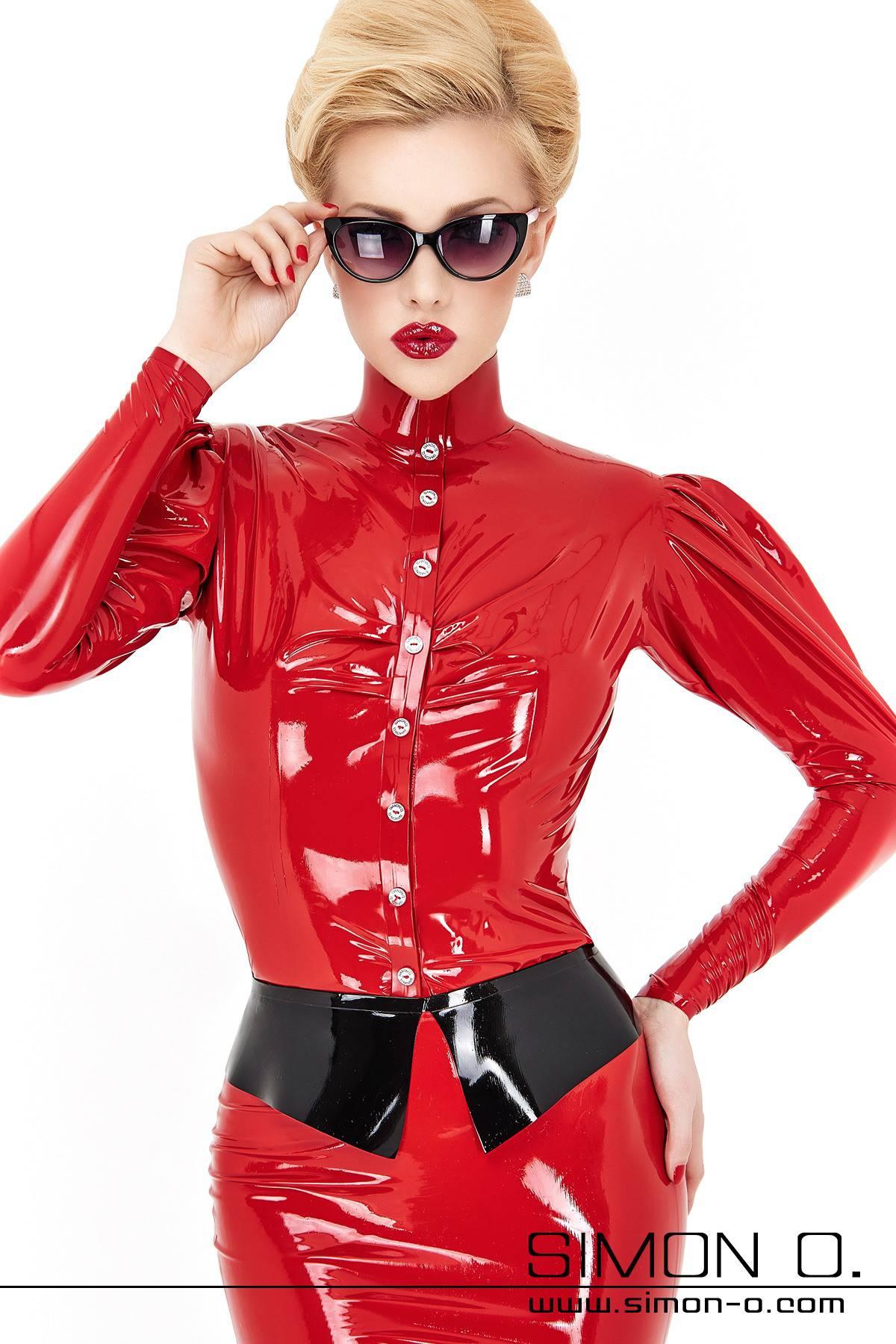 Eine blonde Frau mit Sonnenbrille trägt eine enge glänzende Damen Latex Bluse in Rot mit Stehkragen