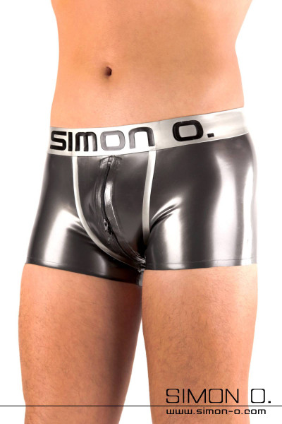 A man wears skintight shiny latex shorts with a Simon O. Logo on the waistband