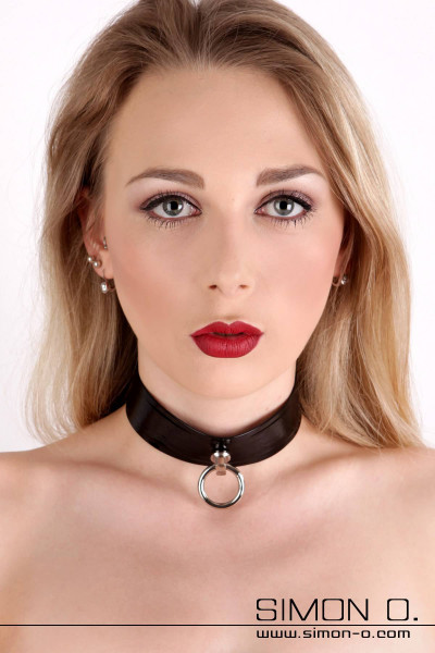 A woman wears a black latex necklace with O ring for the latex slave girl