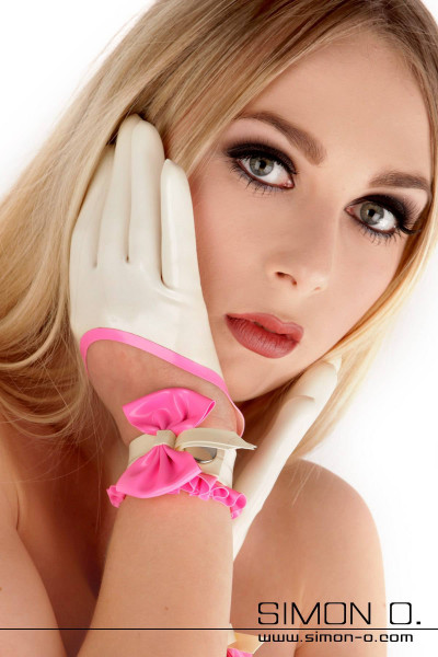 A woman wears short rubber gloves in white with pink and with a mesh and frills.