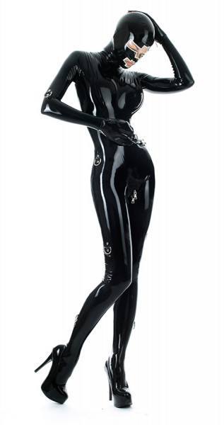 A woman wears a shiny latex bondage catsuit with D-rings and mask