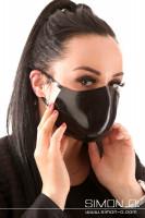 Vorschau: Eine dunkelhaarige Frau trägt einen Latex Mundschutz in Schwarz