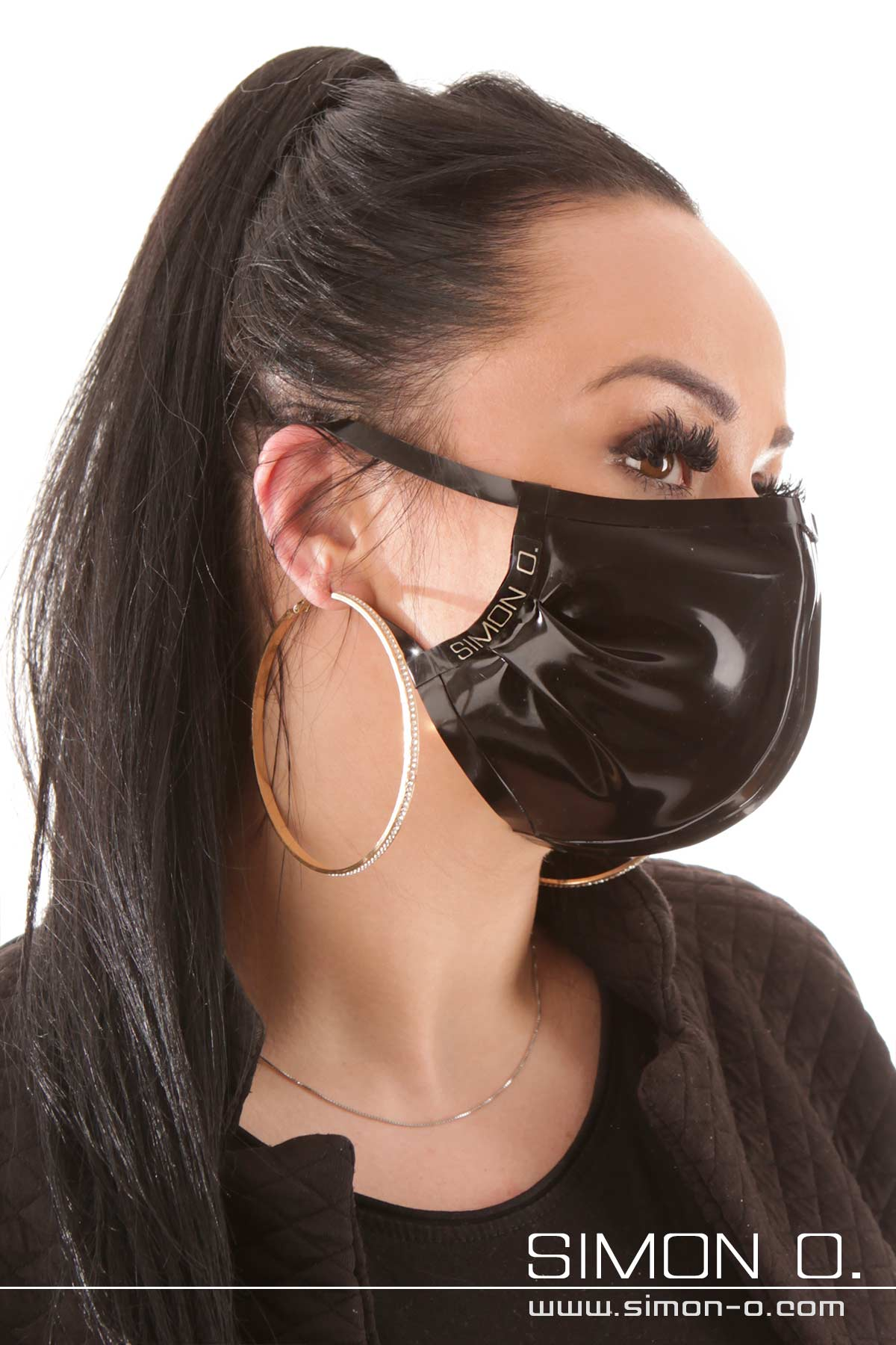 A dark-haired woman is wearing a mouth and nose protector made of latex in black