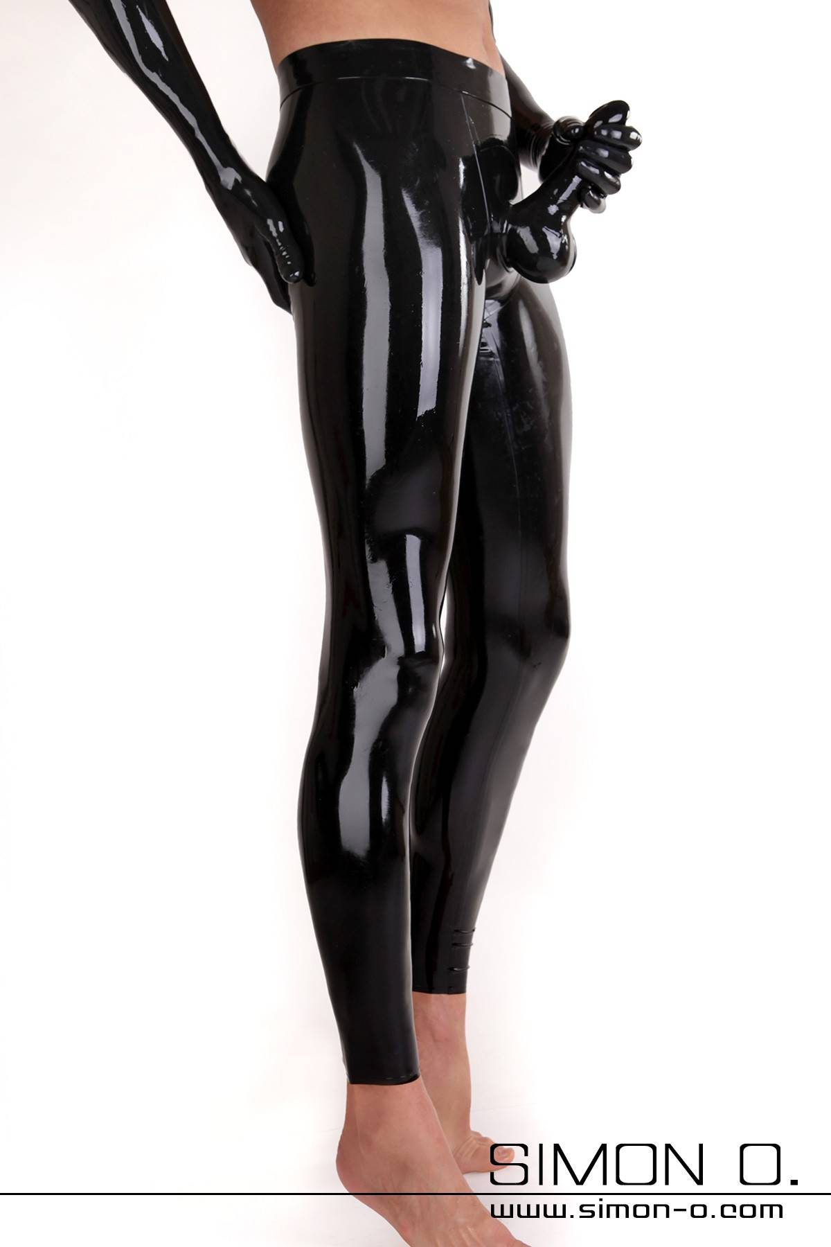 A man wears a skintight latex leggings in black with condom and latex gloves in black