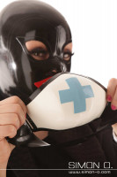 Vorschau: Eine Frau mit latex Maske hält einen Mundschutz in weiß mit Kreuz in den Händen.