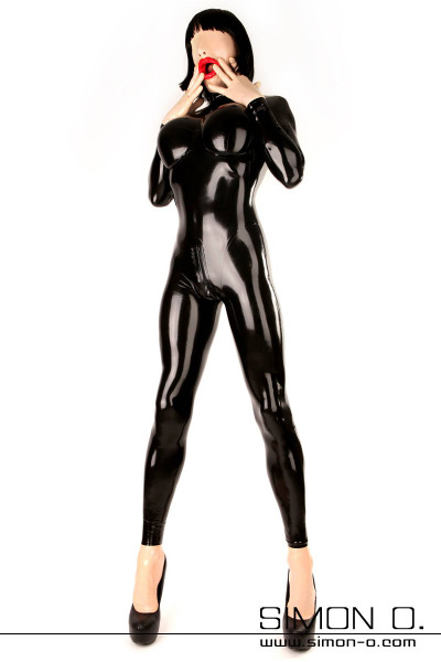 A human rubber doll with a tight black rubberdoll latex catsuit with big boobs with mask gloves and socks in skincolor