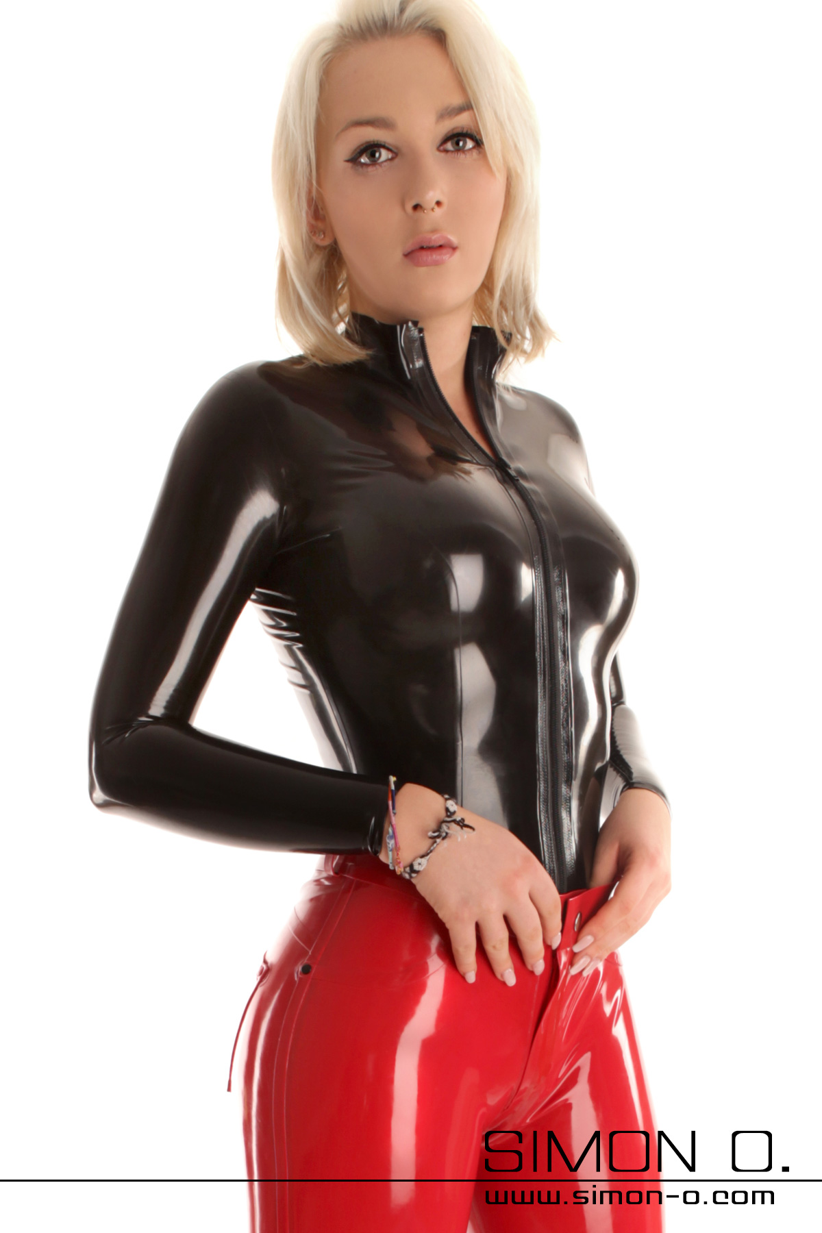 A blonde lady with a tight shine latex top in black with a divisible zipper front