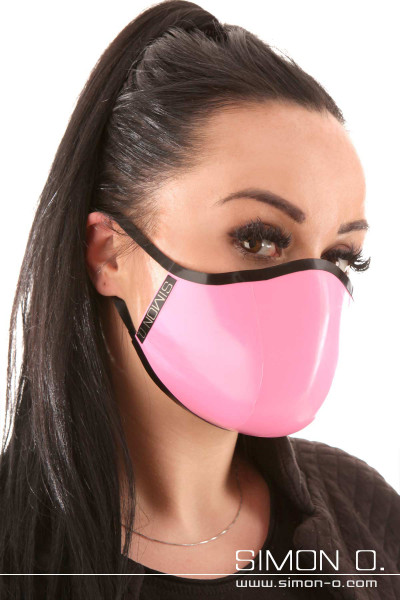 A dark-haired woman is wearing a shiny covid 19 latex face mask in pink