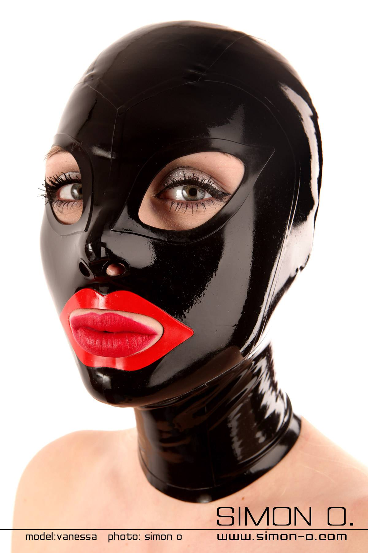 A woman with red lips wears a shiny tight latex hood in black with cat eyes and red mouth