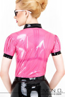 Vorschau: Ein Model mit Sonnenbrille trägt eine kurzarm Latex Bluse in Pink mit Puffärmel und schwarzen Reverskragen von hinten gesehen