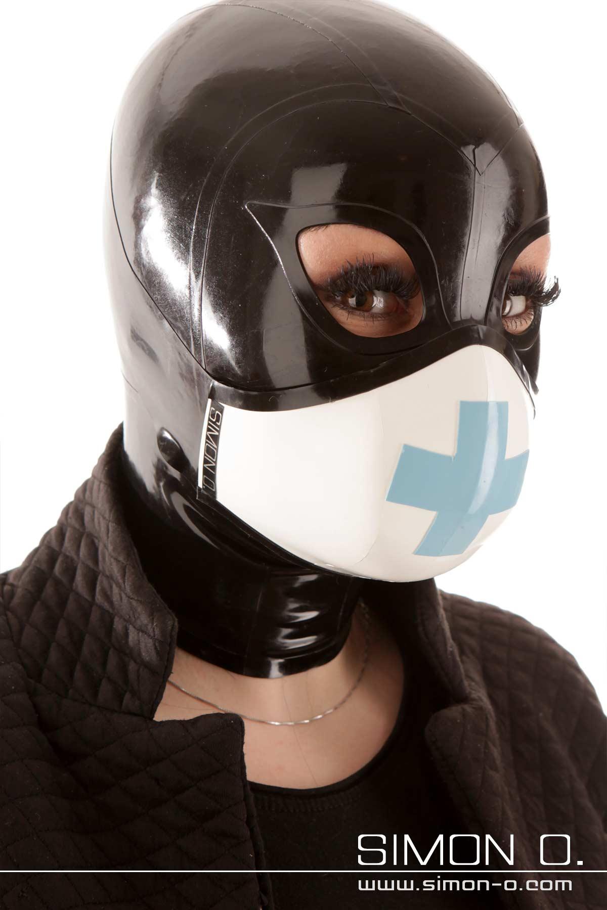 Eine Frau trägt einen Mund und Nasenschutz in Weiß mit einem Kreuz in hellblau über ihrer Latex Maske.
