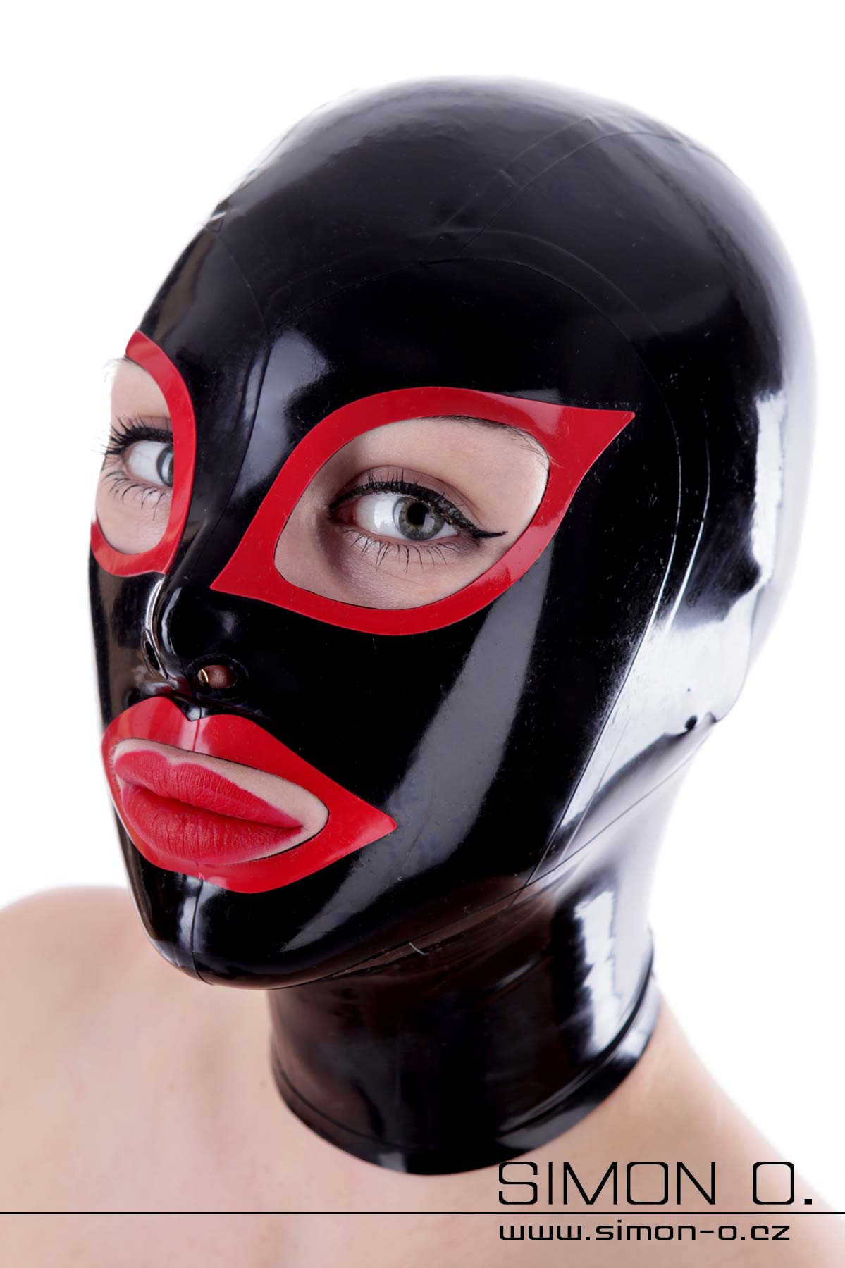A woman wears a latex hood in black with red cat eyes and red kiss mouth.