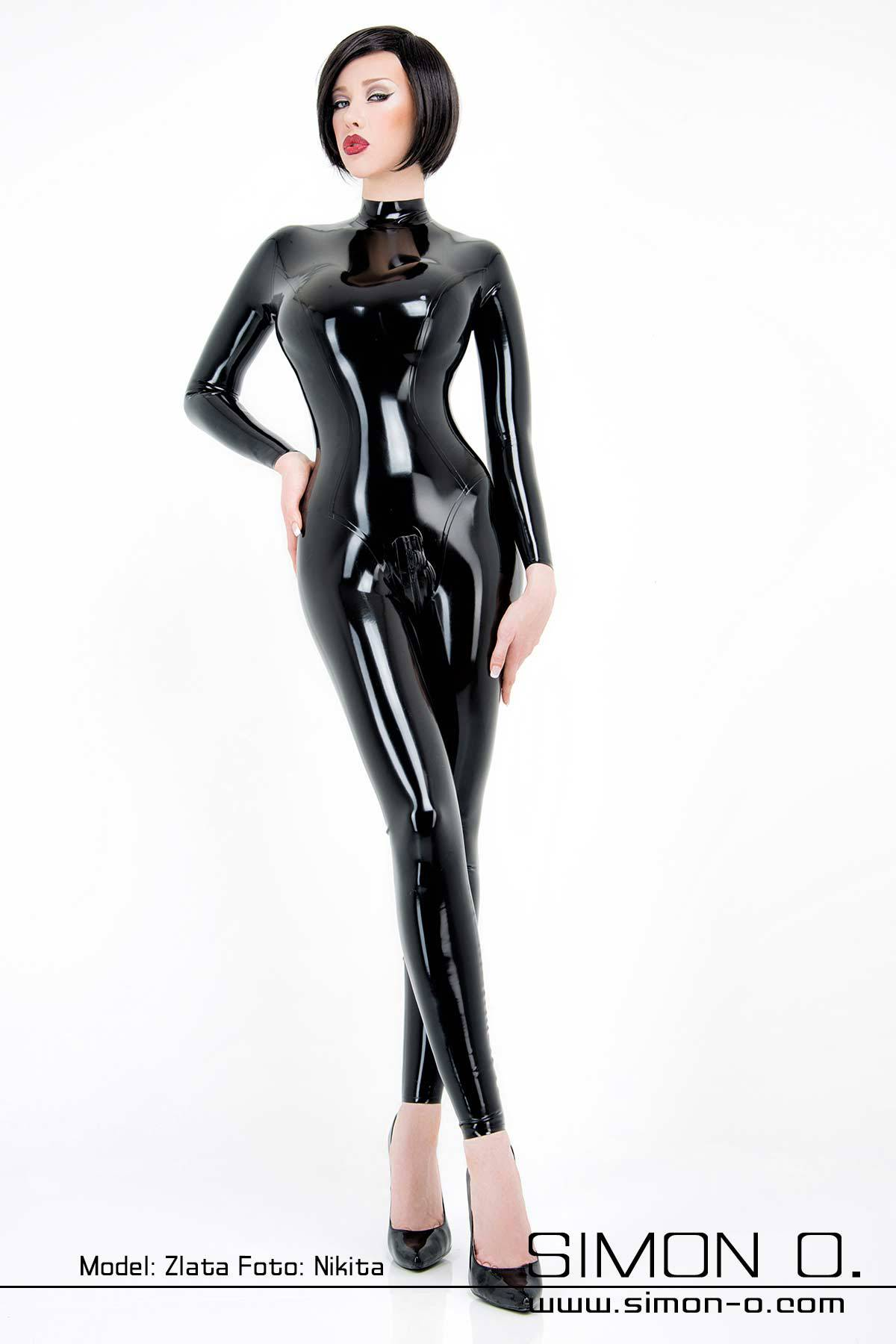 A model wears a shiny skintight black latex catsuit in black with skin tight fit