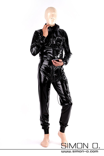 A man in a black wide cut latex suit and he wears a mask socks and gloves made of latex