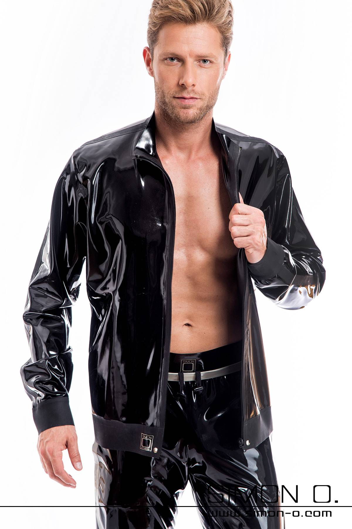A man wears a latex jacket in black with stand-up collar and pockets.