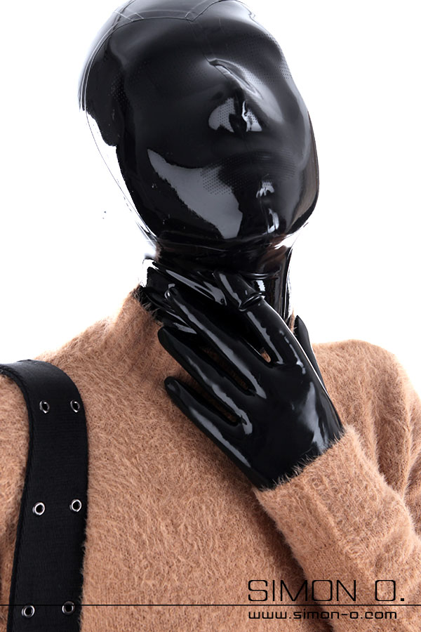 A woman wearing a latex hood mask and latex gloves under a sweater