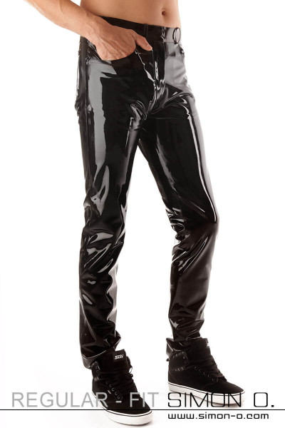 A gentleman wears a shiny latex jean and has a hand in his pocket.