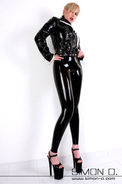 A woman wears a black skintight latex leggings in combination with a leather jacket.