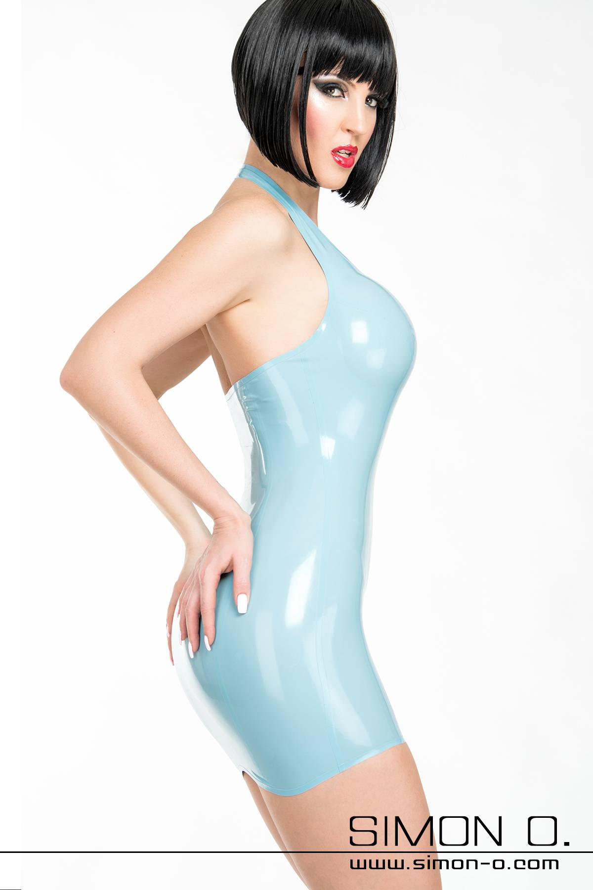A woman wears a light blue halter neck mini dress made of latex. Shiny and close fitting fit
