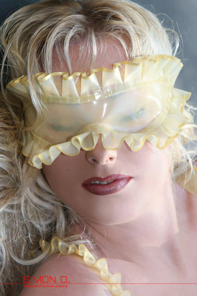 A blonde lady with red lips wears a latex blindfold