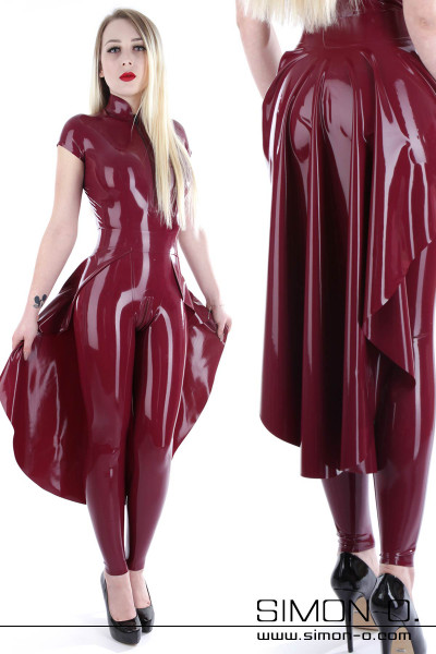 A blonde woman wearing a color fitting latex train over a catsuit